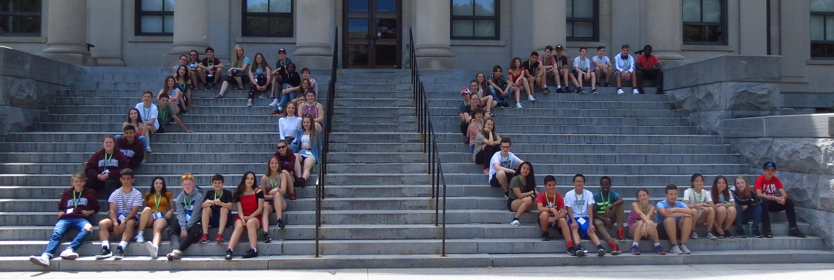 Groupe d'élèves assis dans les marches et formant les lettres DC.